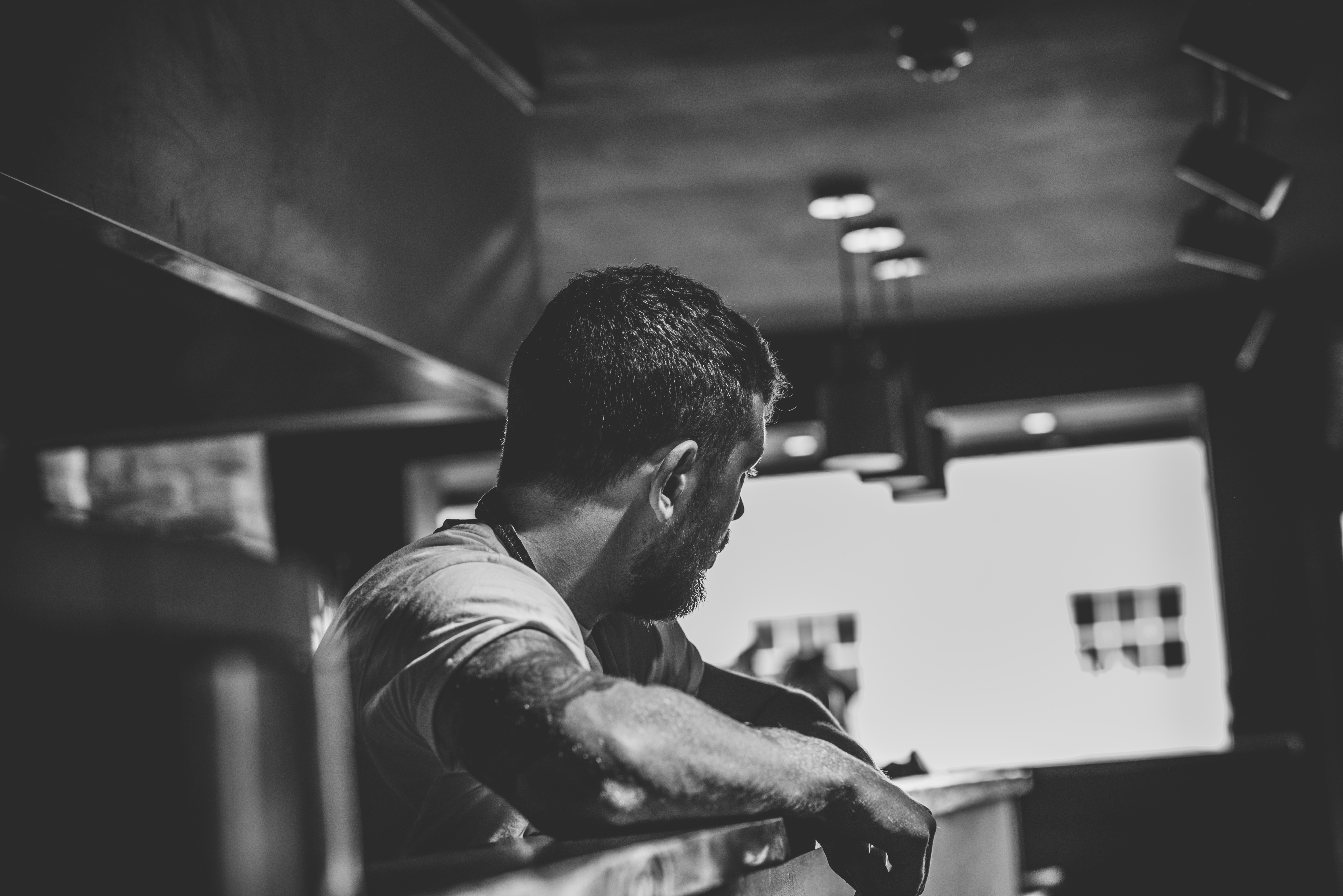 Chef in commercial restaurant kitchen looking at back-of-house