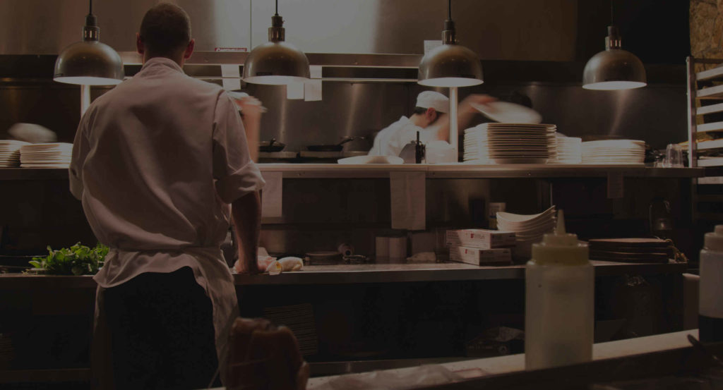 Head chef in commercial restaurant kitchen calling out orders to line cook